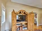 Open the doors to the armoire to reveal a flat-screen TV.