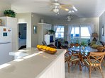 Dining area and living room with access to the unit's private veranda and beach beyond.