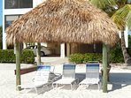 Tiki Huts on the Beach with lounge chairs.