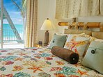 King sized bed in ocean bedroom with private deck overlooking beach and ocean.