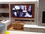 Detalle de la zona frontal con la Television SmartTV y la chimenea.