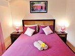 Chambre climatisée côté montagne, meubles et parquet créoles, lit QS