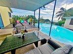 La pièce à vivre, les terrasses donnant sur la piscine et offrant une vue imprenable sur le littoral