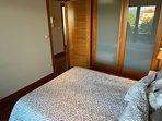 Dormitorio con cama matrimonial, amplio armario con caja fuerte y salida a la terraza