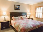 King sized bed with two bedside tables and lamps, large window, making the bedroom bright and cheery.