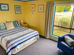 Main bedroom, shower room adjacent, television, 'tub' chair and garden view