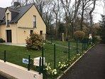 Vue générale de la maison et du jardin fleuri avec barbecue en angle.