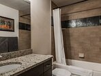 Guest bathroom with Granite Vanity, Tiled Tub & Shower Combination