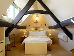 The master bedroom is in the beautiful eaves of the cottage