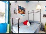 Dormitorio cama doble de 1,35 y ventilador de techo con salida a Patio