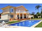 Vista general de la casa, piscina, solarium y jardín