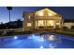 la casa al atardecer con la iluminación de la piscina