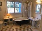 Bathroom with flush toilet, clawfoot tub and pedestal sink.