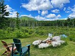 Large firepit with seating on logs for 10 people adjacent to the pond and views of Whiteface Mountain.