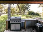 Outdoor kitchen with gas grill and refridgerator.