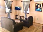 Small but comfortable living room with cable and smart TV just in the event one needs it.
